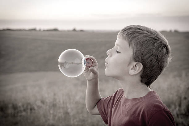 Boy blowing up the soap bubbles